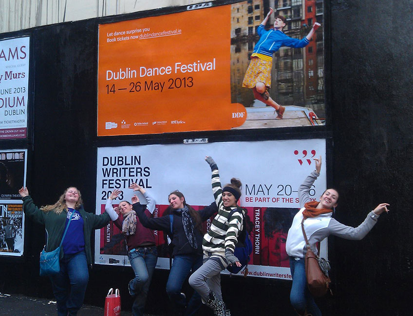 TCC students on a Dublin sidewalk posing in front of wall poster for Dublin Dance Festival