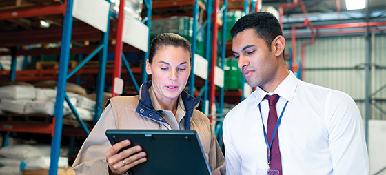 Female worker showing younger male worker information on a computer inside a warehouse