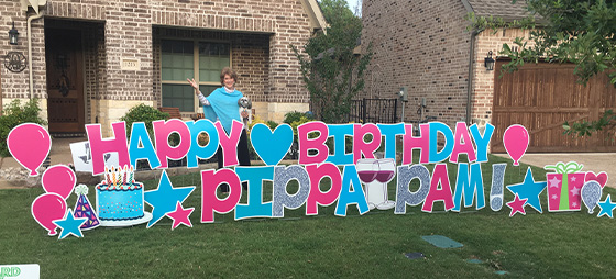 Pamela Quinn posing with her dog behind her Happy Birthday sign in her yard