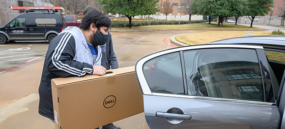TCC staff member putting computer into a car