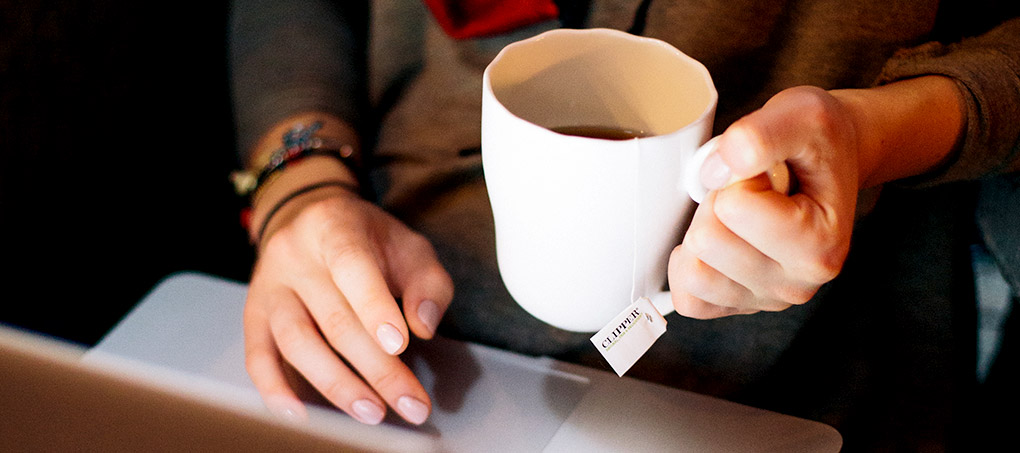 A student holds a mug of coffee and works on a laptop