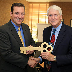 Alan Goben receives the key to campus from Larry Darlege