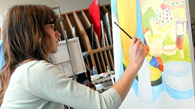 A student artist paints at an easel