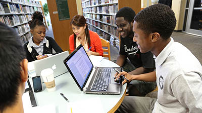 A group of students study together in the library