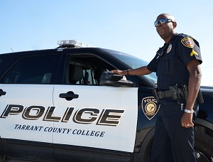 TCC Police Officer posing with a TCC Police car