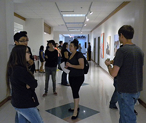 guests mingling and looking at artworks during an opening for an exhibit at the Art Corridors Galleries