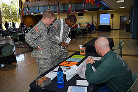 Military students looking at information on a table