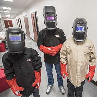 three welding students wearing protective clothes and head gear