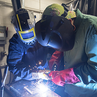 welders in protective head and body gear welding