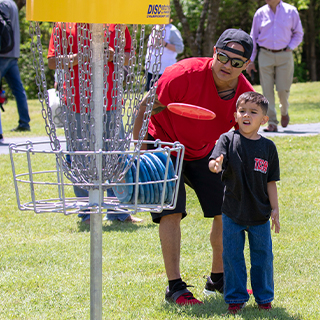 A man and young boy playing disc golf