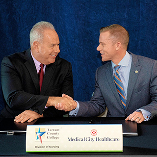 Chancellor Giovanni shaking hands with Medical City Healthcare