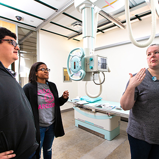a female radiologic technology instructor showing a male student and a female student how to use a piece of radiology equipment
