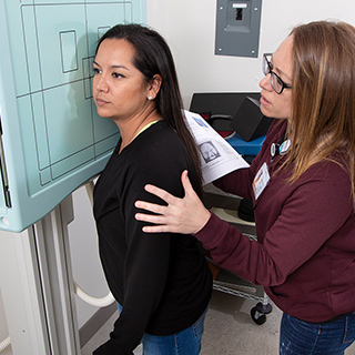 a female student practicing placing another female student's head to take a radiologic image
