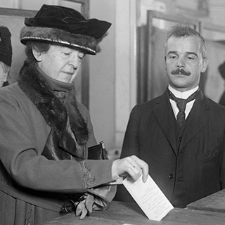 vintage photo of a woman putting a paper ballot in and ballot box