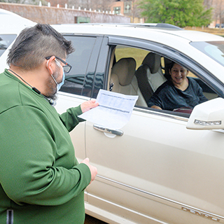 Man looking at student schedule of student waiting in a car